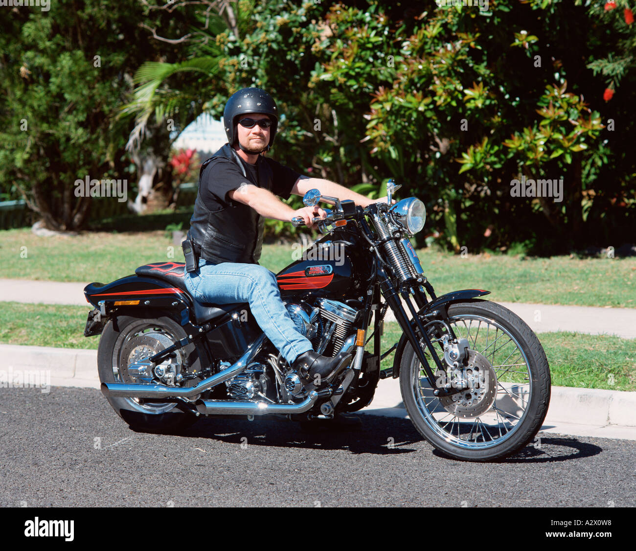 Man riding Harley Davidson motorcycle on suburban street Stock Photo