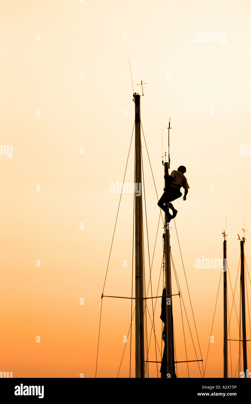 A Sillouette of a person at the top of a yachts mast at sunset. - Stock Image