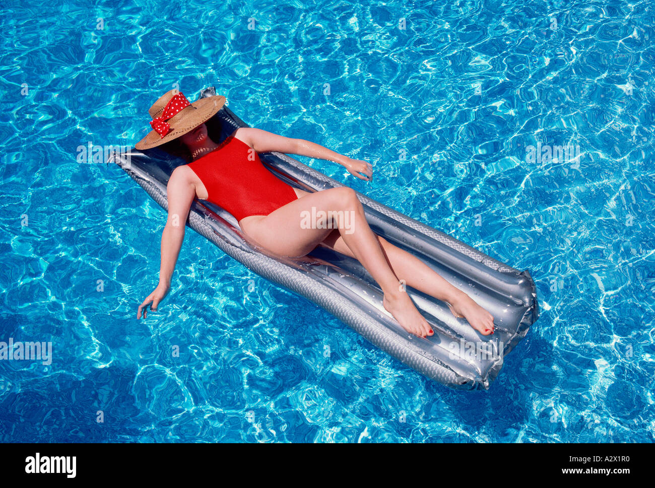 Young woman in red, one-piece swimsuit floating on airbed in ...