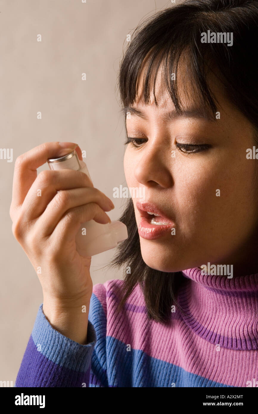 Woman using bronchial inhaler to relieve asthma symptoms. - Stock Image