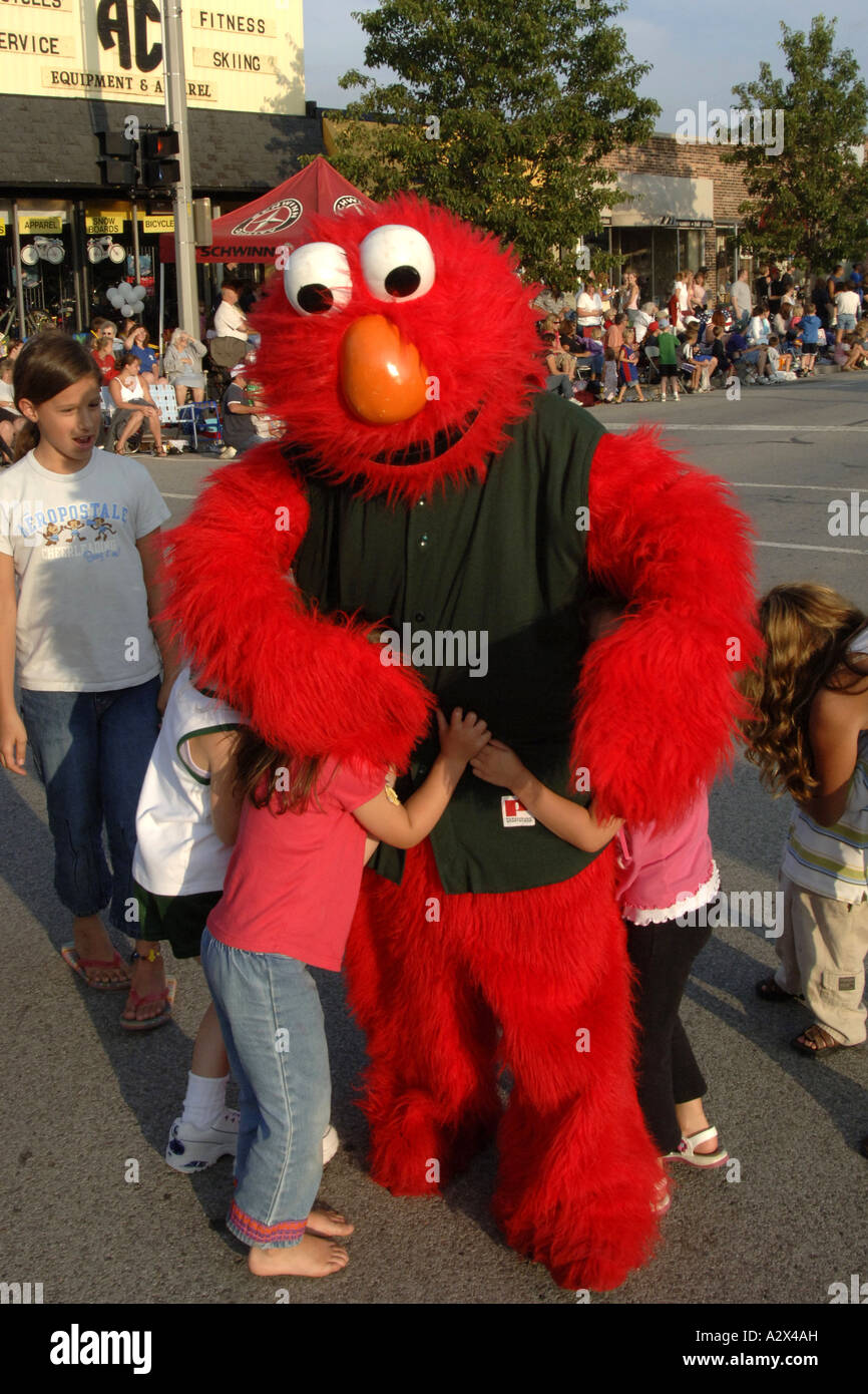Children surrounding Elmo as he walks in a street parade - Stock Image