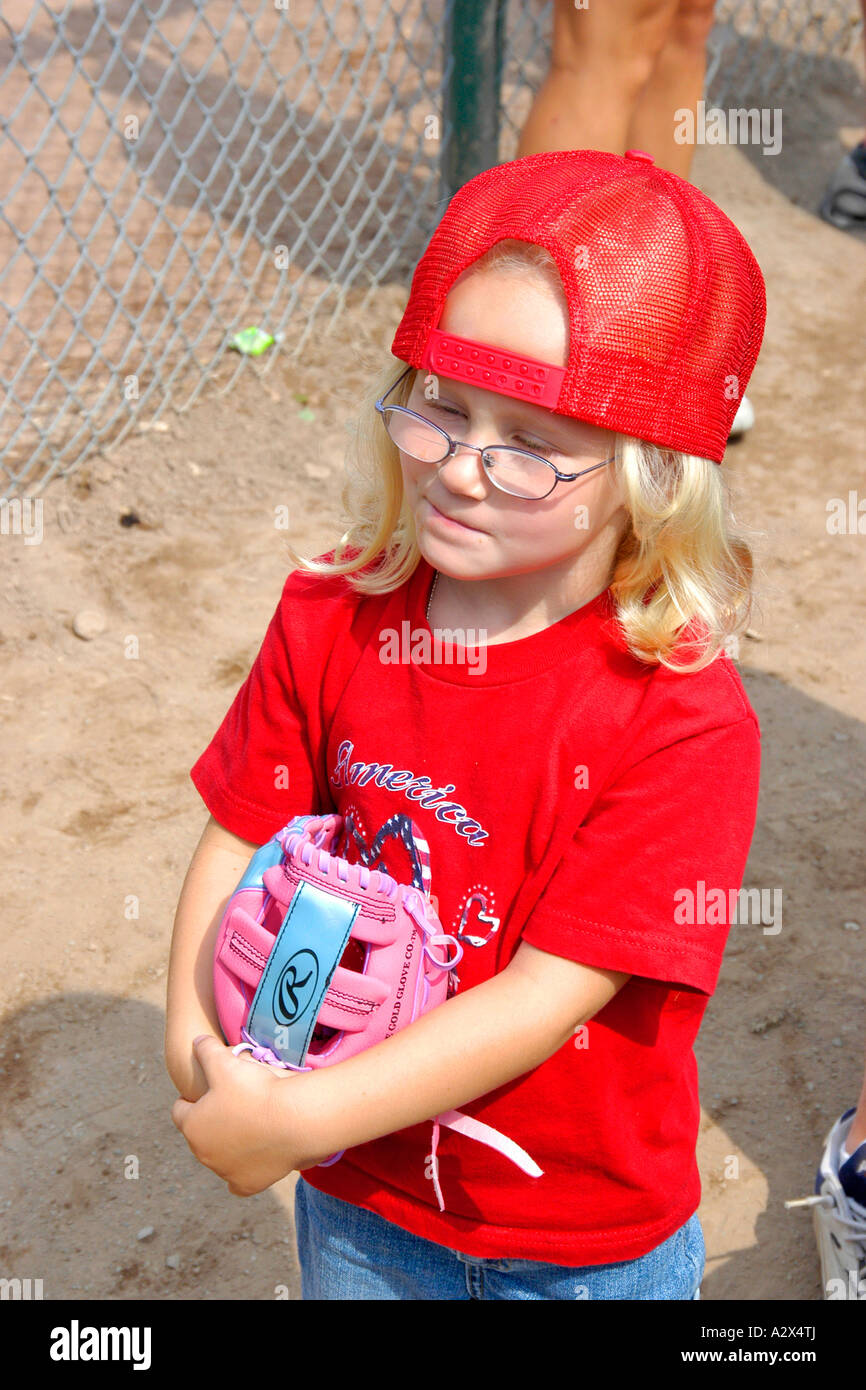 small pre k female wearing a red baseball hat having a snack at a