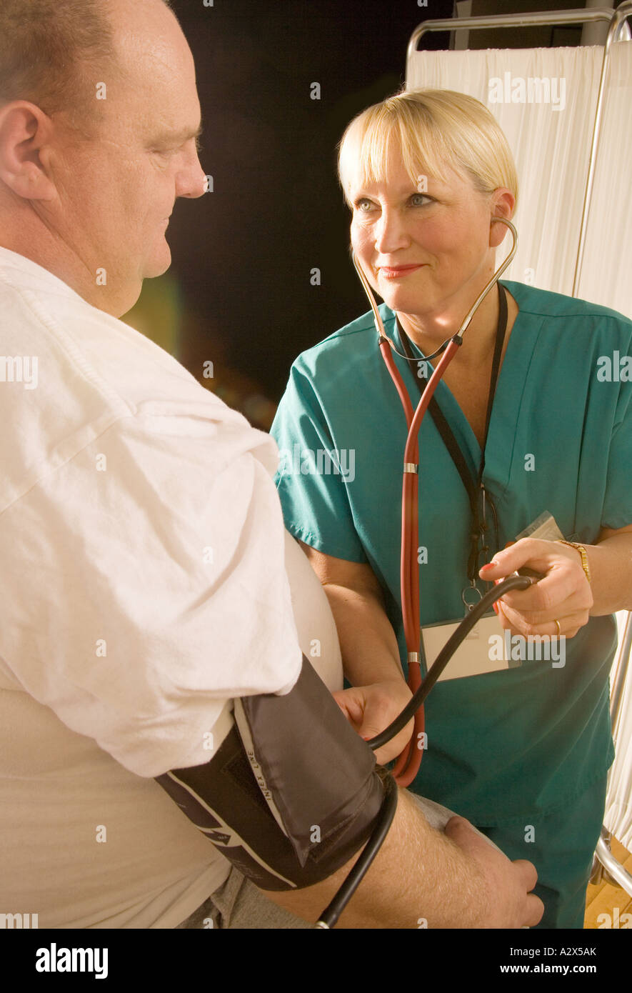 Nurse taking the blood pressure reading from an overweight patient. - Stock Image