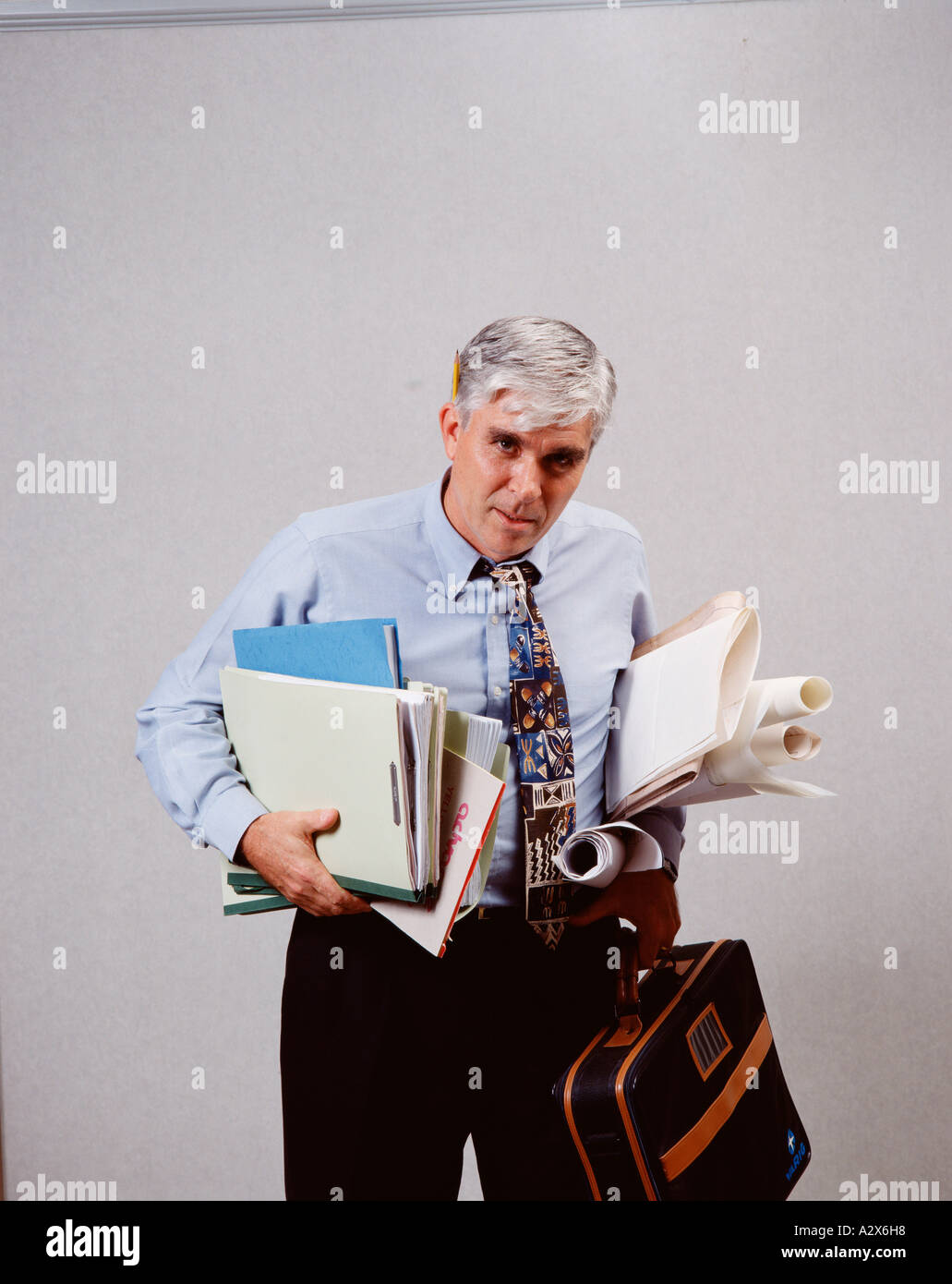 Middle aged man holding paperwork and looking stressed and overworked. - Stock Image