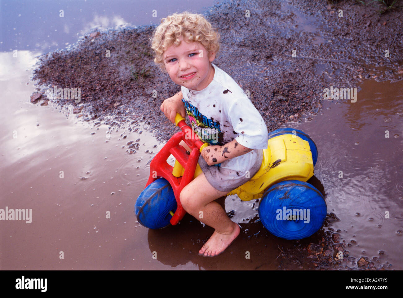 Little boy child outdoors riding plastic tricycle - Stock Image