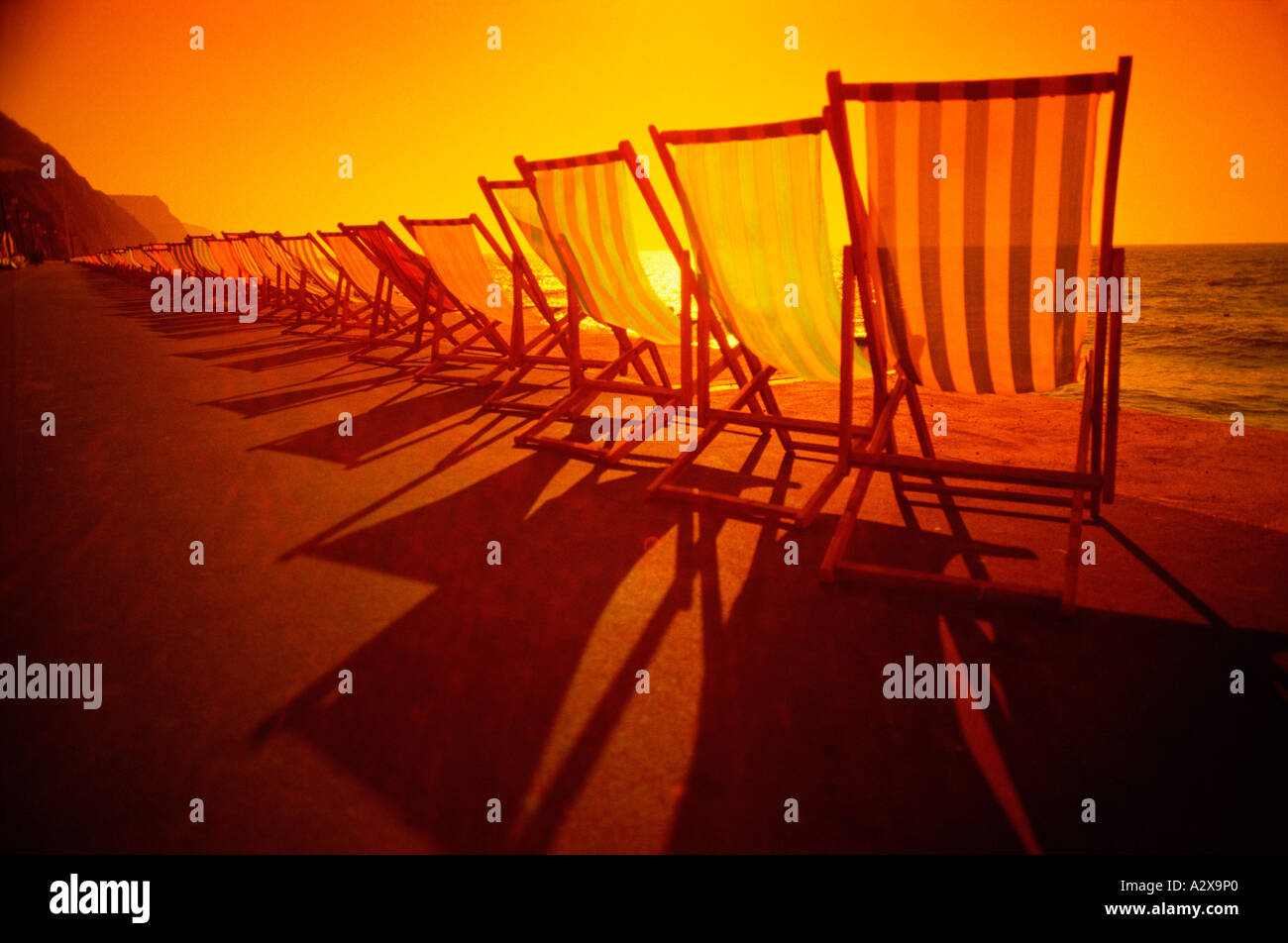 United Kingdom. England. Row of deckchairs on seafront promenade back lit at sunset. - Stock Image