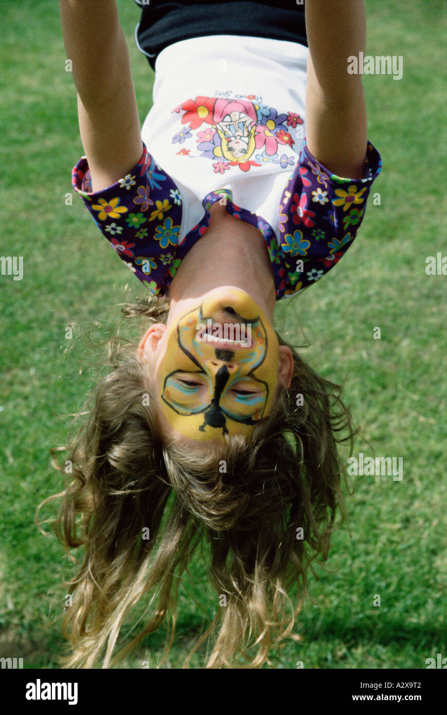 Outdoor image of child girl with painted face hanging upside down. - Stock Image