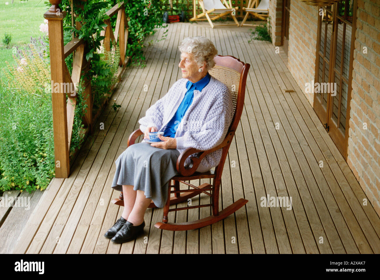 Old Woman Sitting In Rocking Chair On Veranda At Home.   Stock Image