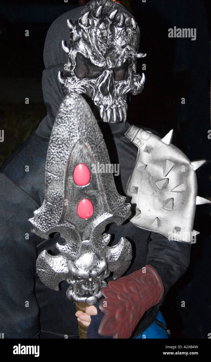 Halloween trick or treater wearing a masked warrior costume with spear age 14. St Paul Minnesota USA - Stock Image