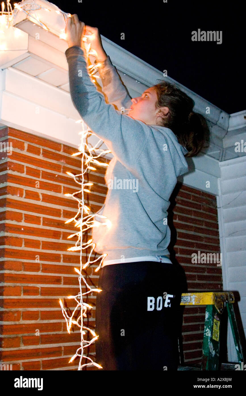 What Can I Use To Attach Christmas Lights To Brick teen age 15 hanging christmas lights after dark on a ladder