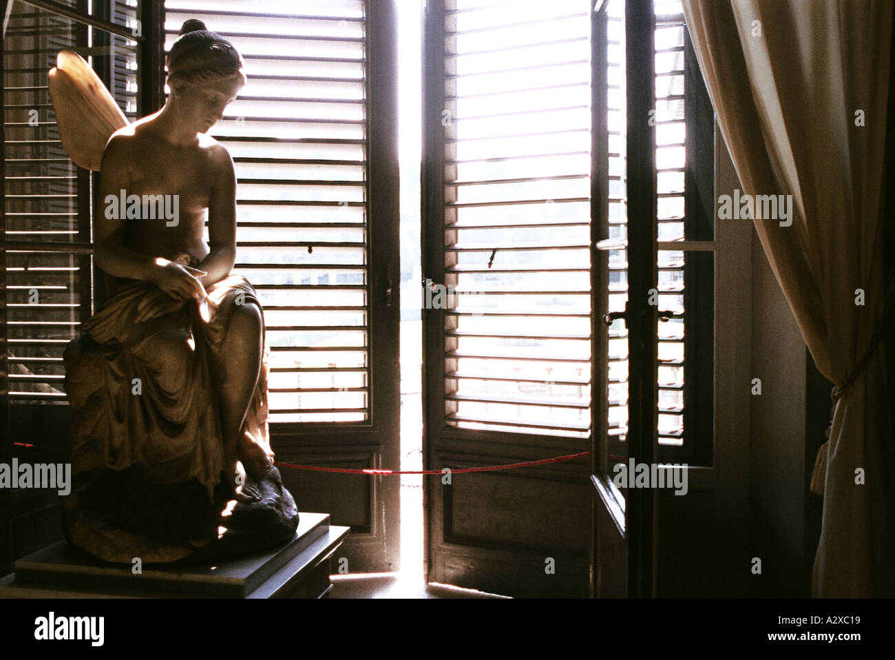Carved Stone Statue Of Angel In Front Of Slightly Open Wooden Window  Shutters In Window In Florence, Italy