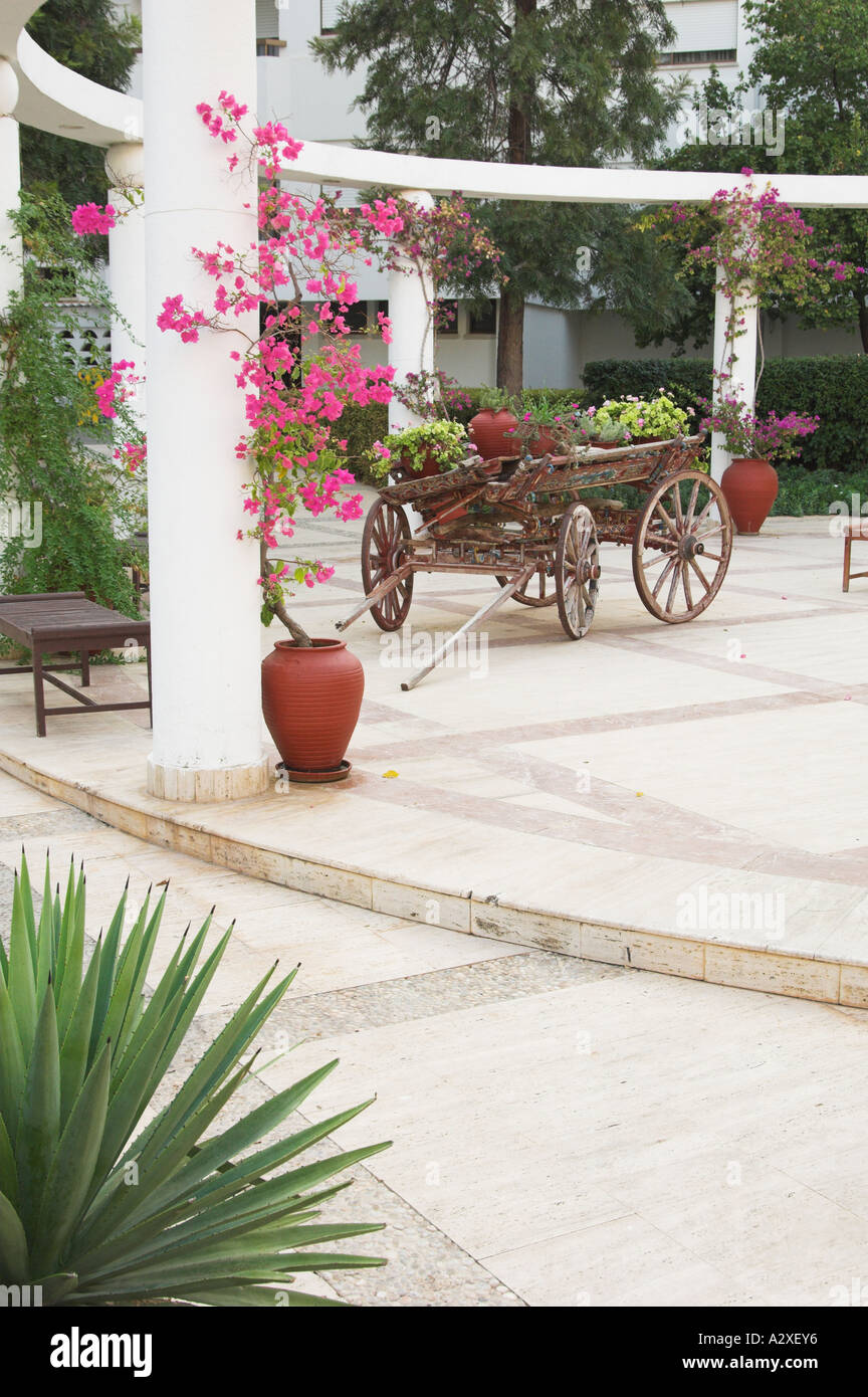 The resort courtyard decor of an old wooden wagon and bougainvillea flowers at the Jasmine Court Hotel in Girne, Cyprus - Stock Image
