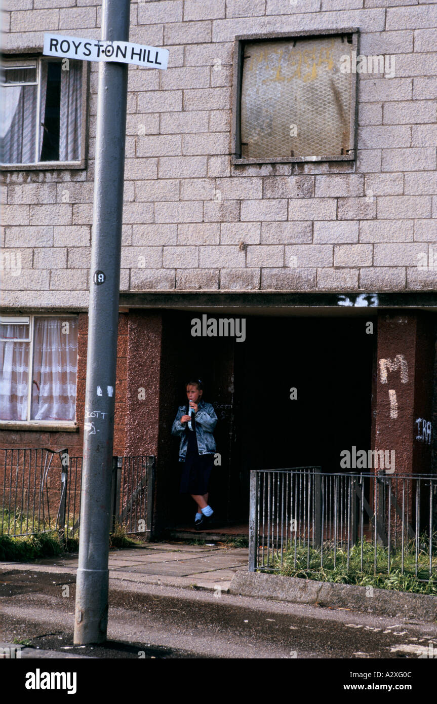 A school girl waits for a friend in Possil Park, a run-down neighbourhood in Glasgow - Stock Image