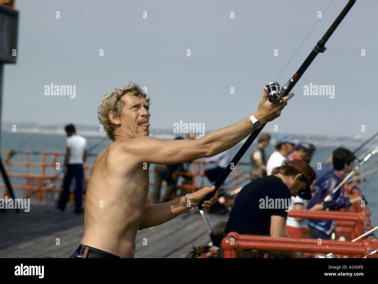 bare chested sport fisherman sticking tounge out of mouth while casting with rod line - Stock Image