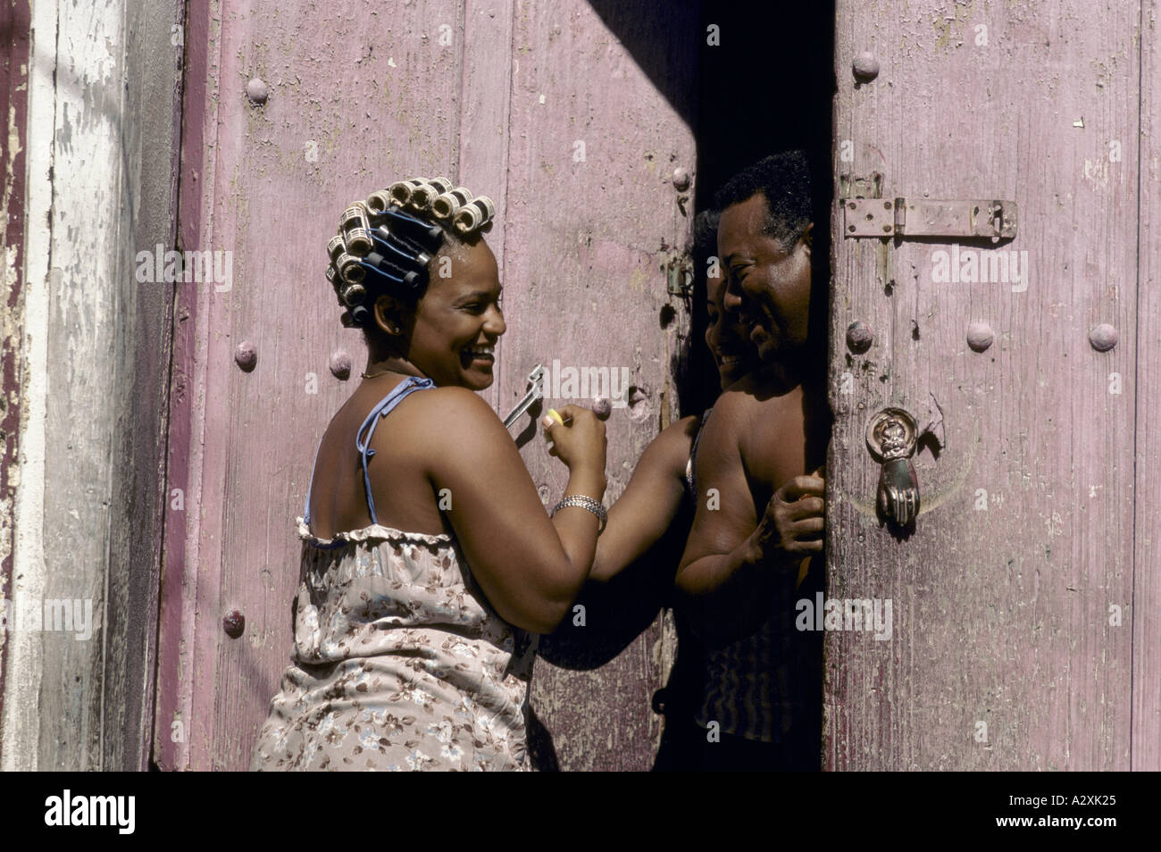 Woman with curlers in her hair having a laugh with a man on their front door in 'Old Town', Havana, Cuba - Stock Image