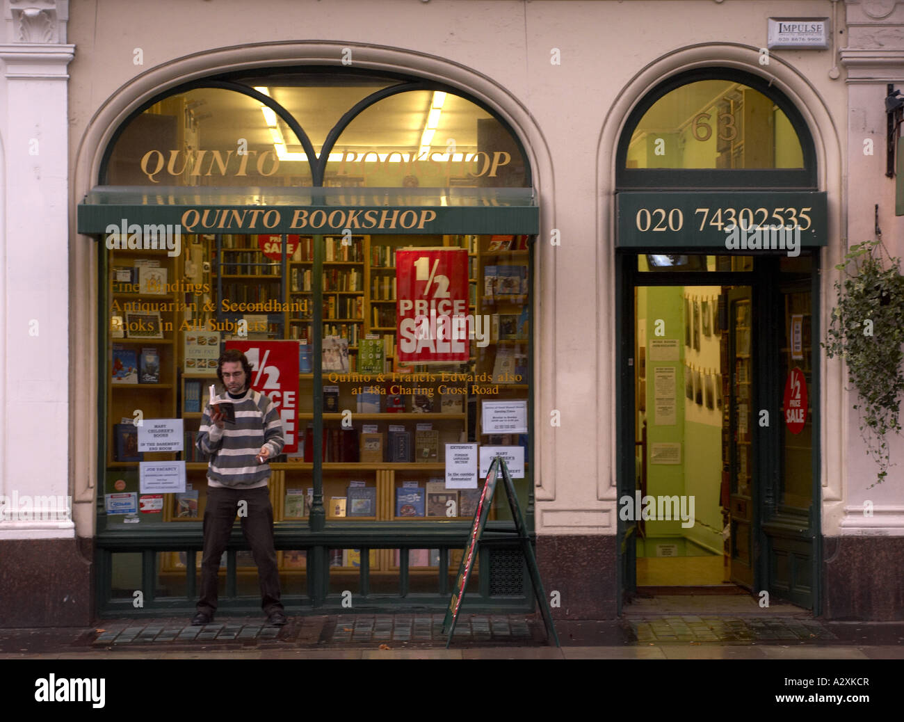 Man reading in front of Quinto Bookshop rare and antique books Stock