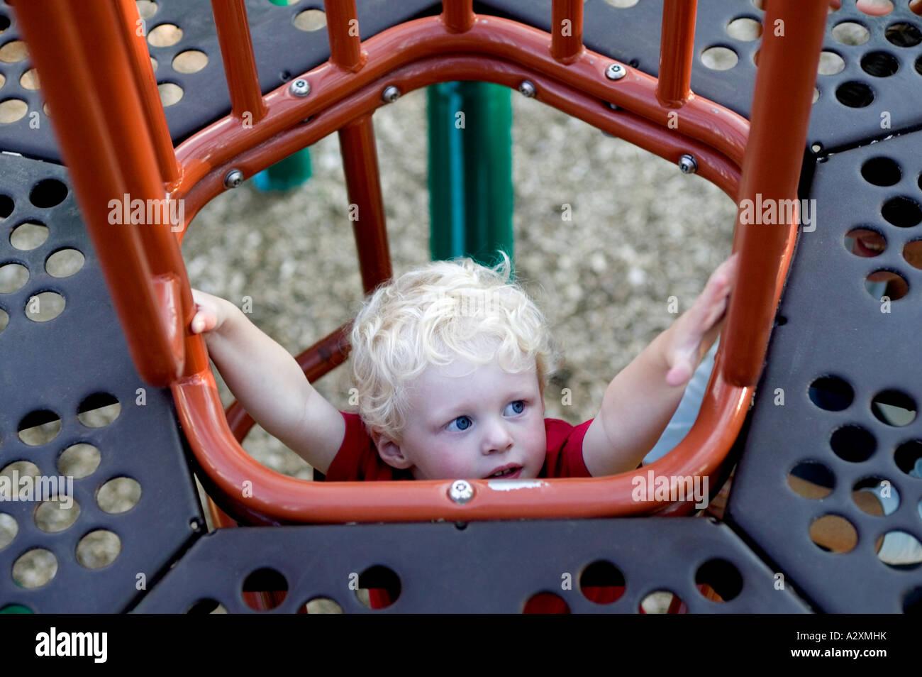 Toddler Boy Climbs Jungle Gym On Town Playground, Salida, Colorado, USA - Stock Image