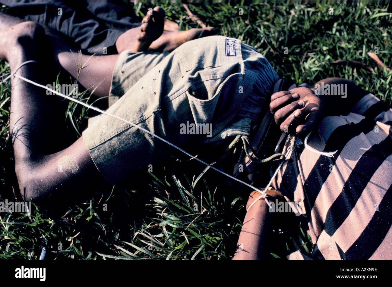 Rio de Janeiro, Brazil.  The bodies of two teenage boys tied up and dumped in a field had been murdered the night before. - Stock Image
