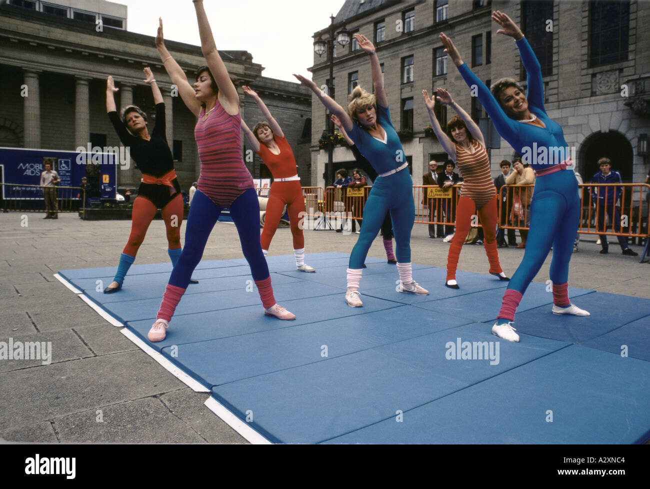 group of women doing aerobics exercise class outdoors in city square 1983 Stock Photo