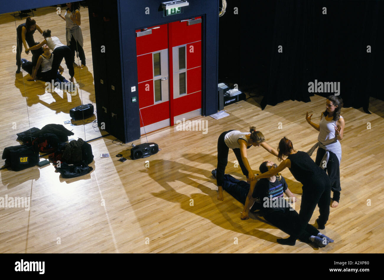 Female dance students confer as they try out body moves & shapes during rehearsal in Liverpool Institute Of Performing Arts - Stock Image