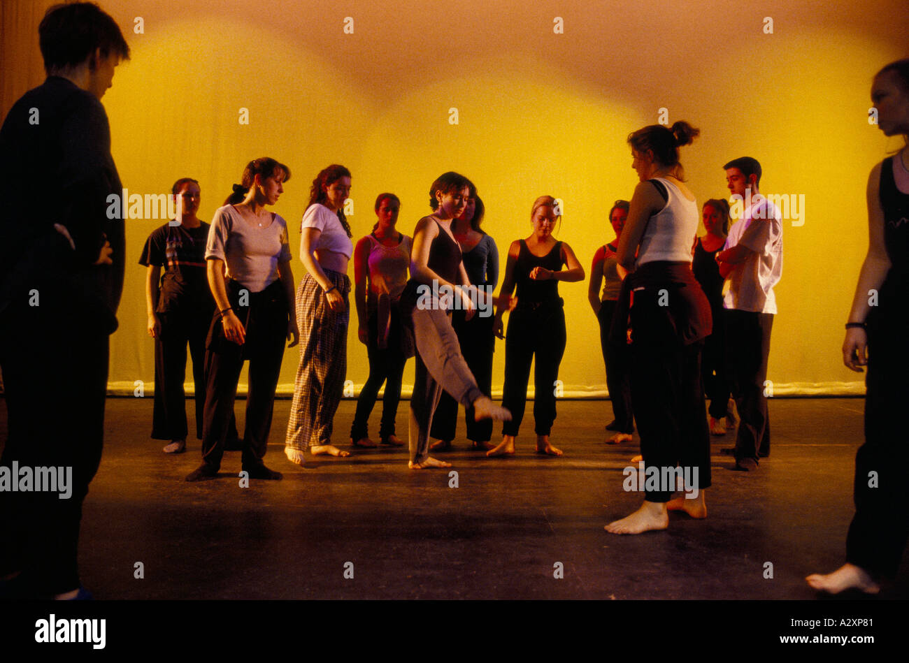 Dance students watch as one girl trys out a pointing leg movement during rehearsal at Liverpool Institute Of Performing Arts - Stock Image