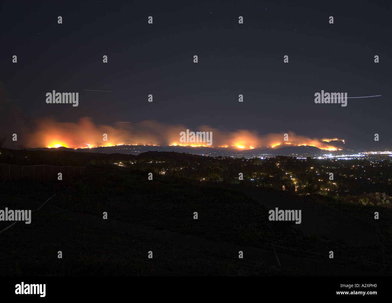 17 second exposure reveals aircraft trails during wildfire. - Stock Image