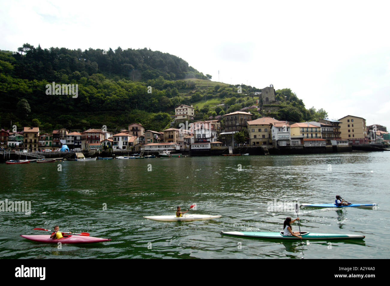 Children canoeing opposite the town of Pasajes San Juan near San Sebastian,Spain - Stock Image