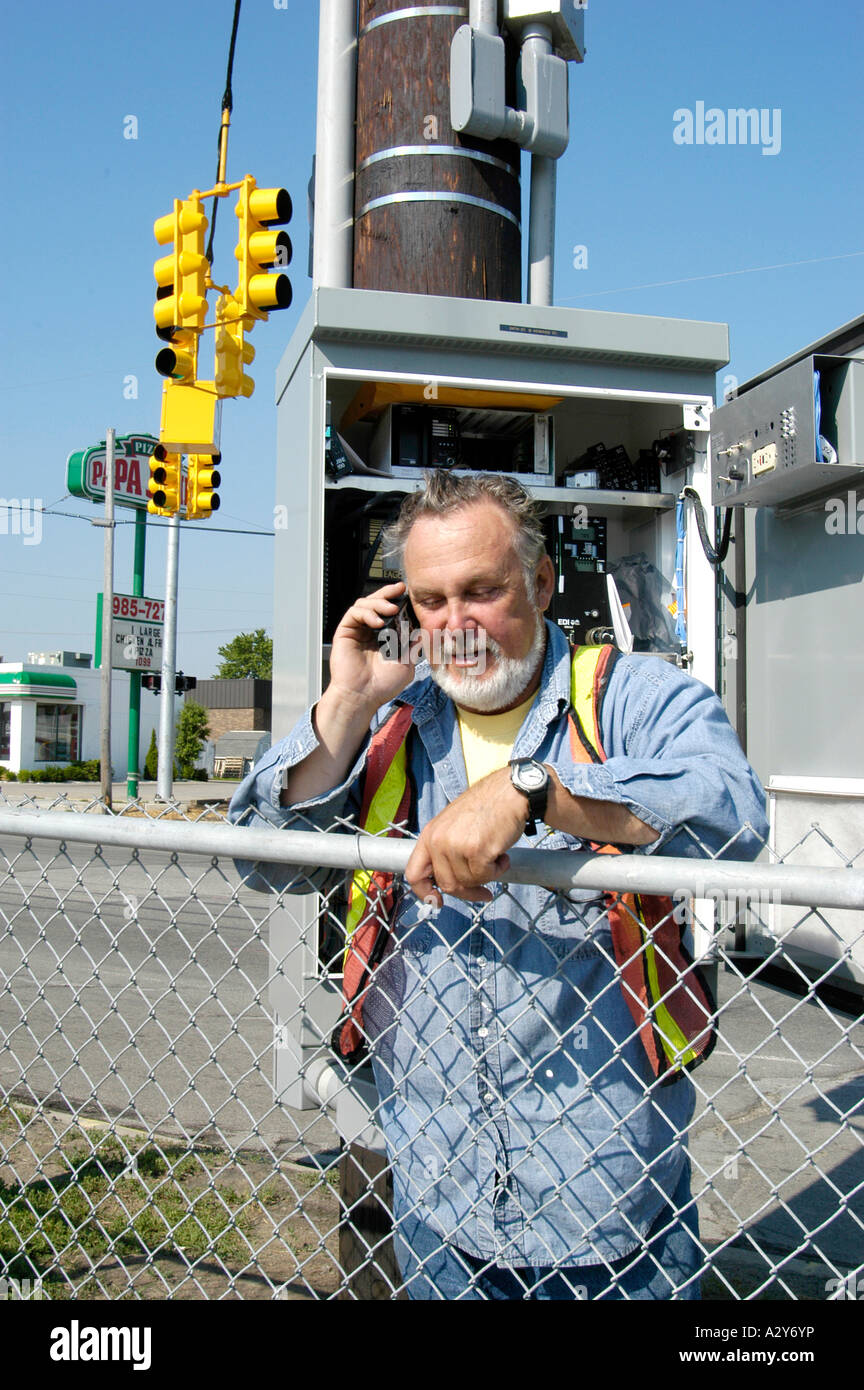 Adult male telephone technician works on a communications problem outside Stock Photo