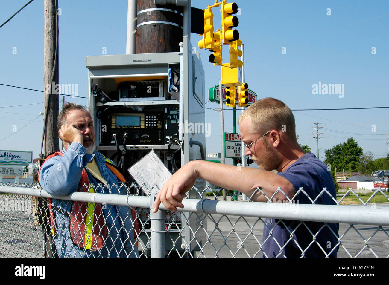 Adult male telephone technician works on a communications problem outside - Stock Image