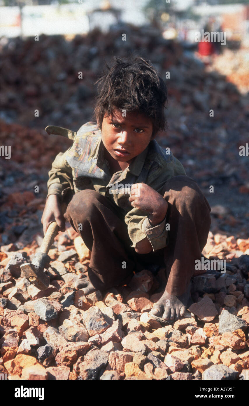Young boy using hammer to break bricks to be used to mend roads Punjab india - Stock Image