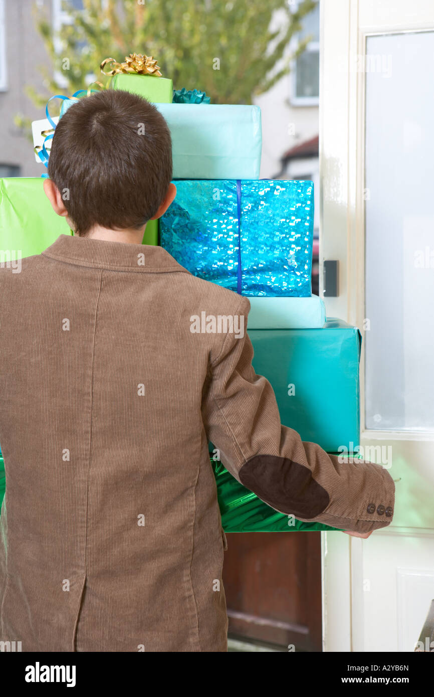 Aboy carrying a pile of presents out of a front door shot from the back. - Stock Image