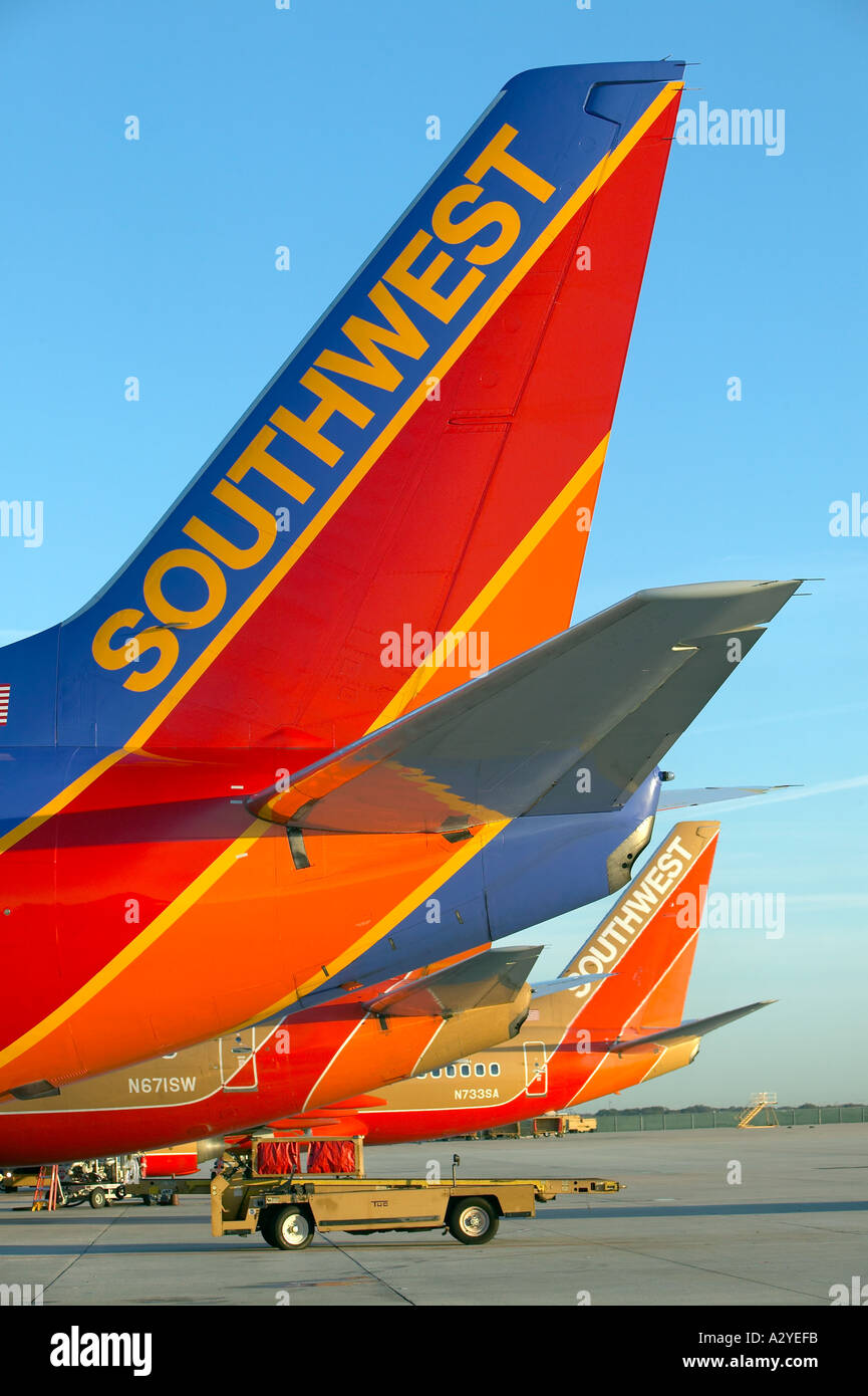 Southwest passenger airline tails airside with baggage car - Stock Image