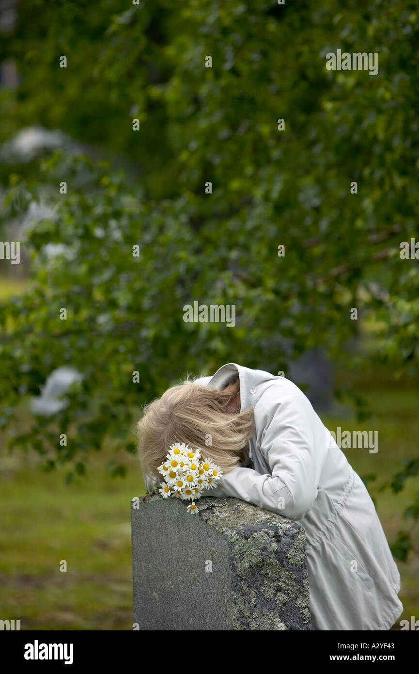 senior 50s 60s Caucasian woman with daisies lays head on granite grave stone marker - Stock Image