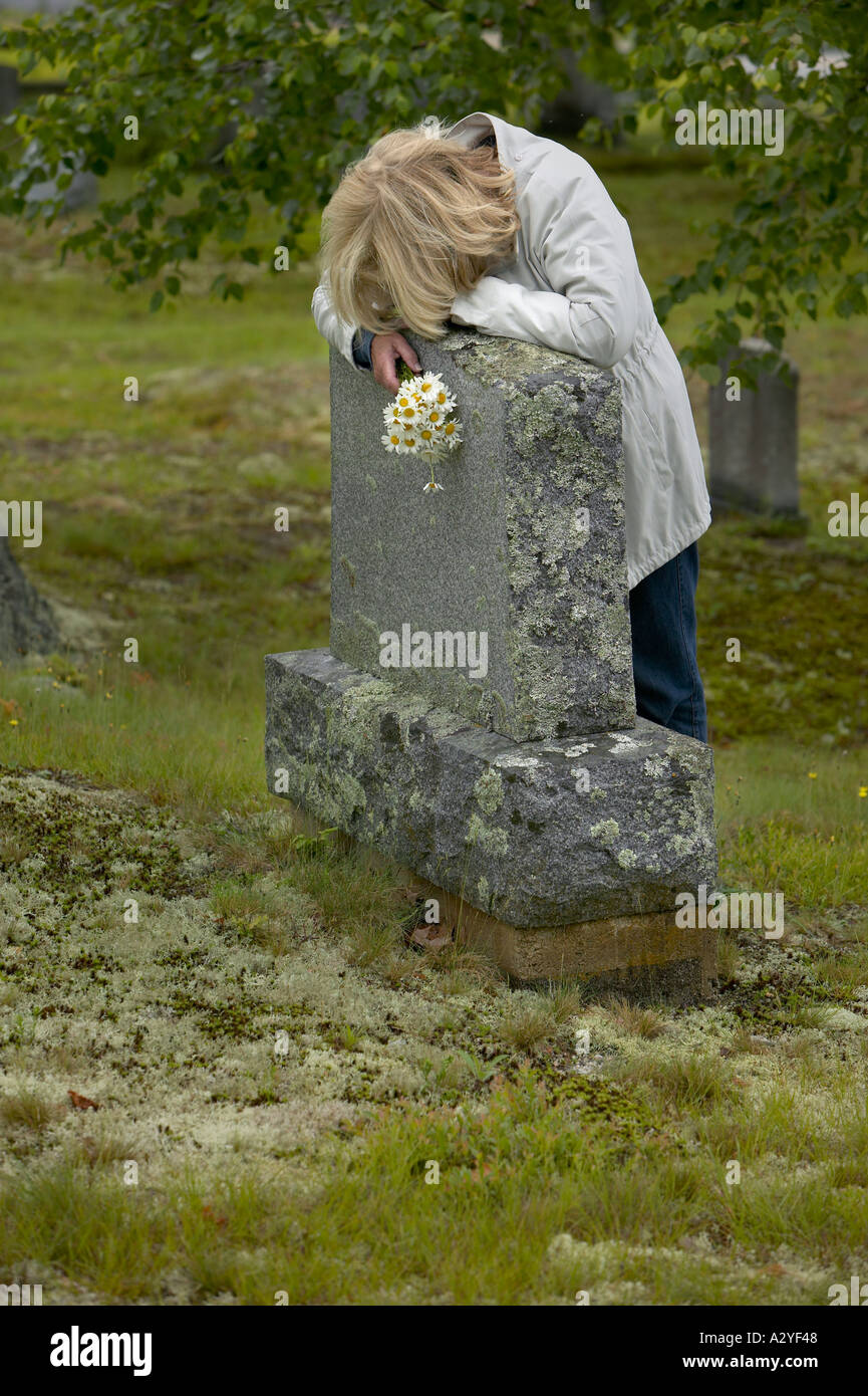 Late 50 s caucasian woman with daisies lays head on head stone marker with large tree in background and moss covered ground - Stock Image