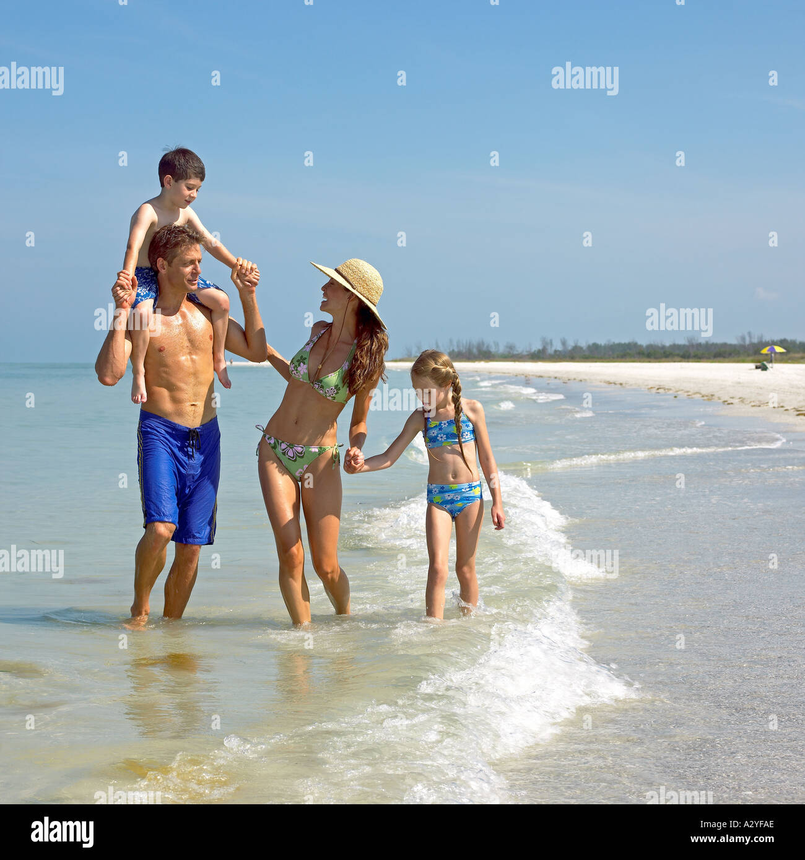 Caucasian family walks in surf Stock Photo