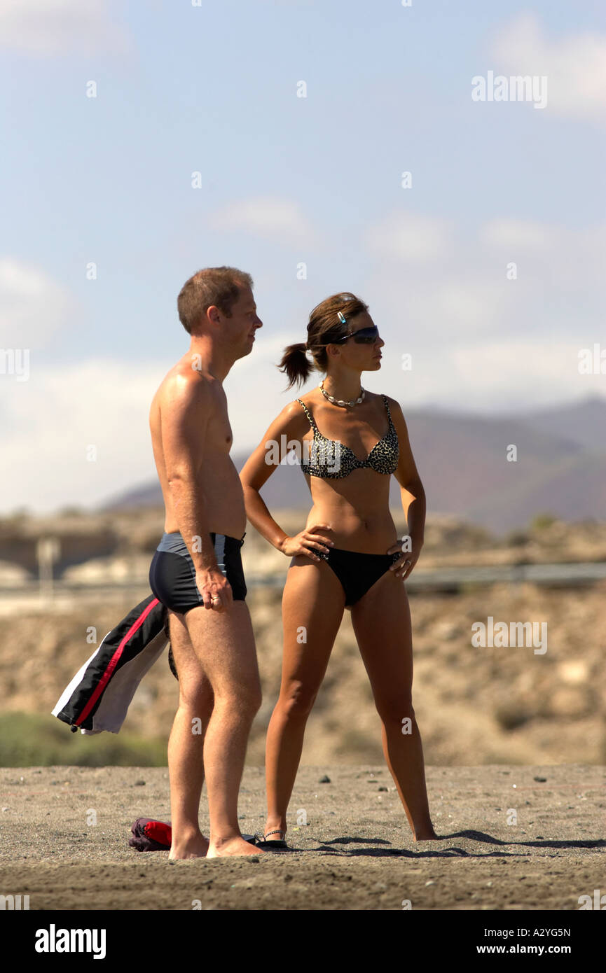 late 20s twenties couple standing on El Medano beach Tenerife Canary Islands Spain - Stock Image