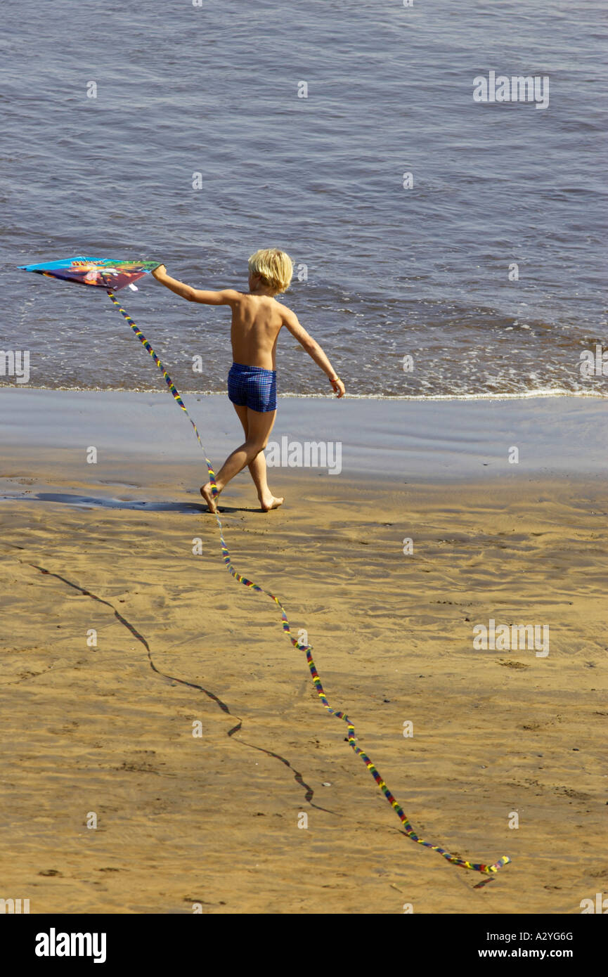 young blonde haired boy playing with kite on the seashore on El Medano beach Tenerife Canary Islands Spain - Stock Image