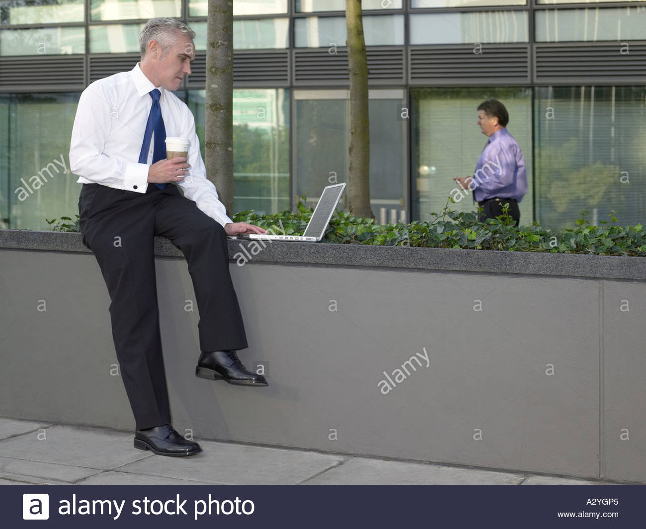 Office worker using laptop computer on a wall - Stock Image
