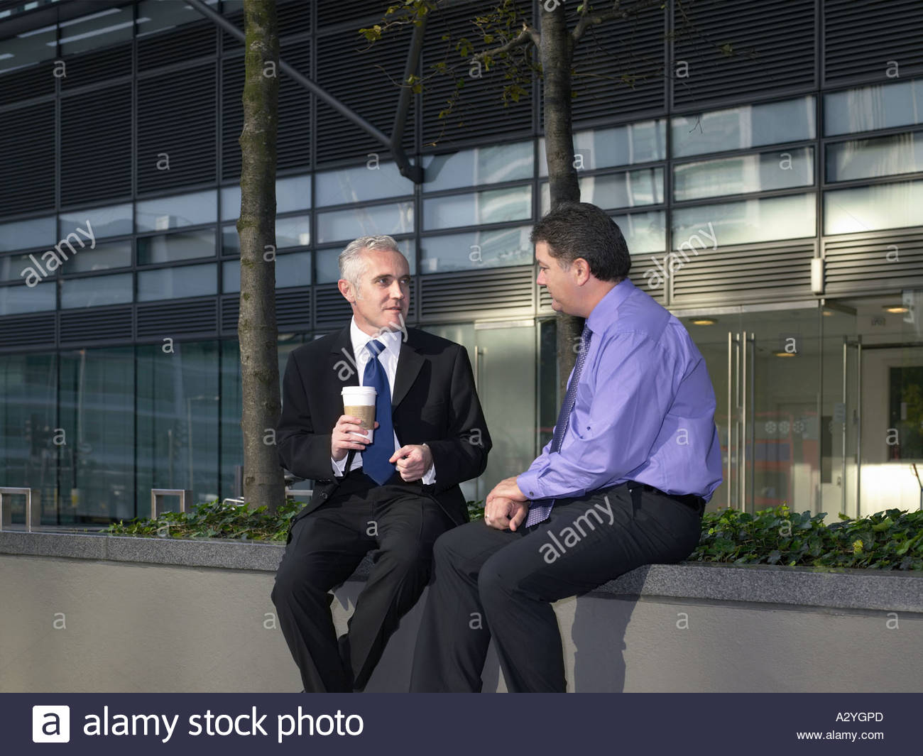 Businessmen talking on a wall - Stock Image