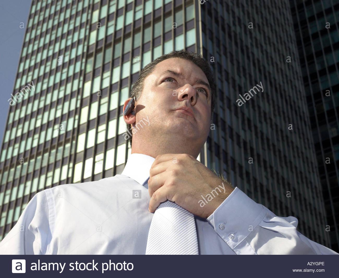 Businessman adjusting his necktie - Stock Image
