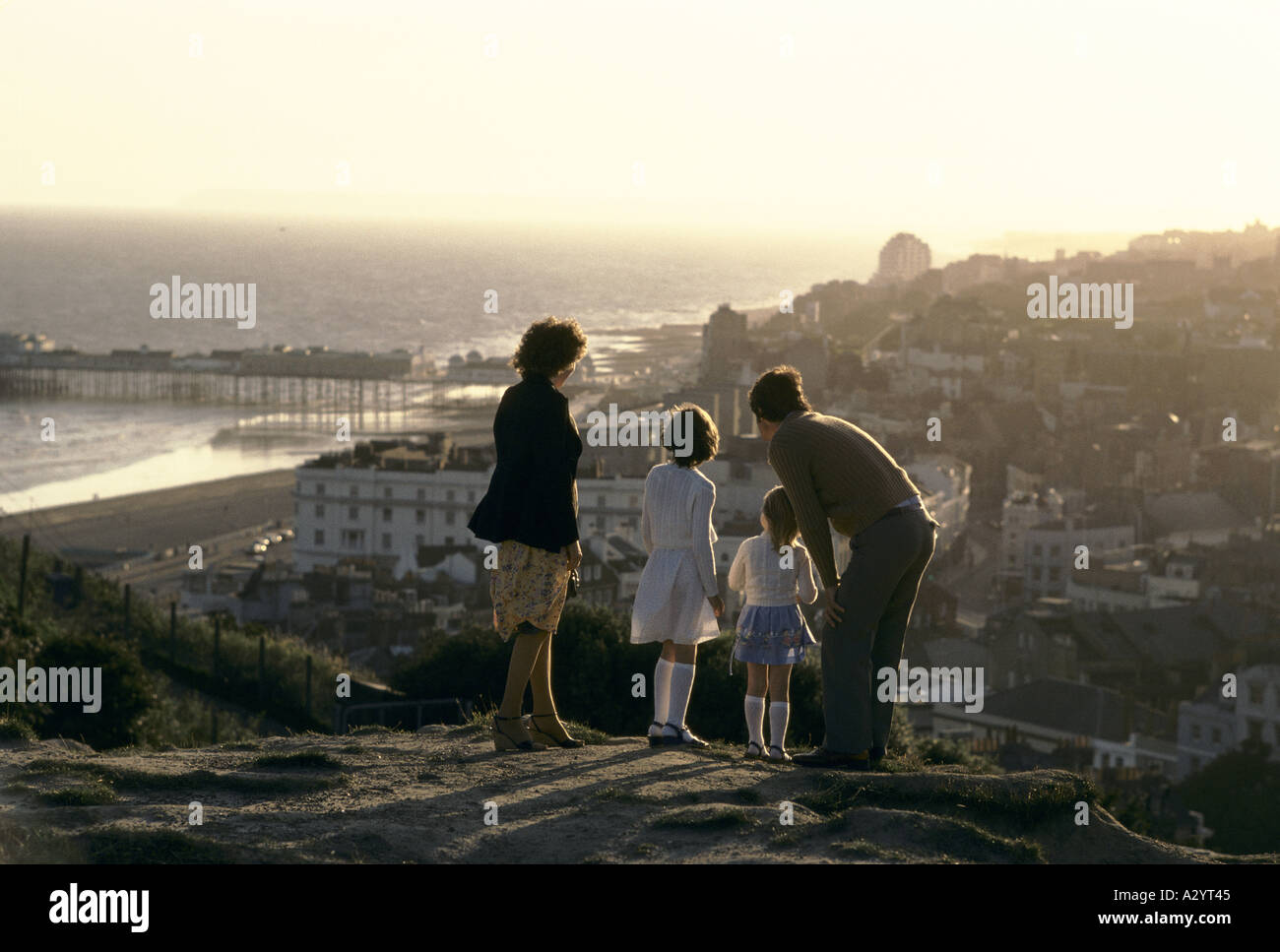 family on hill overlooking seaside town at sunset - Stock Image