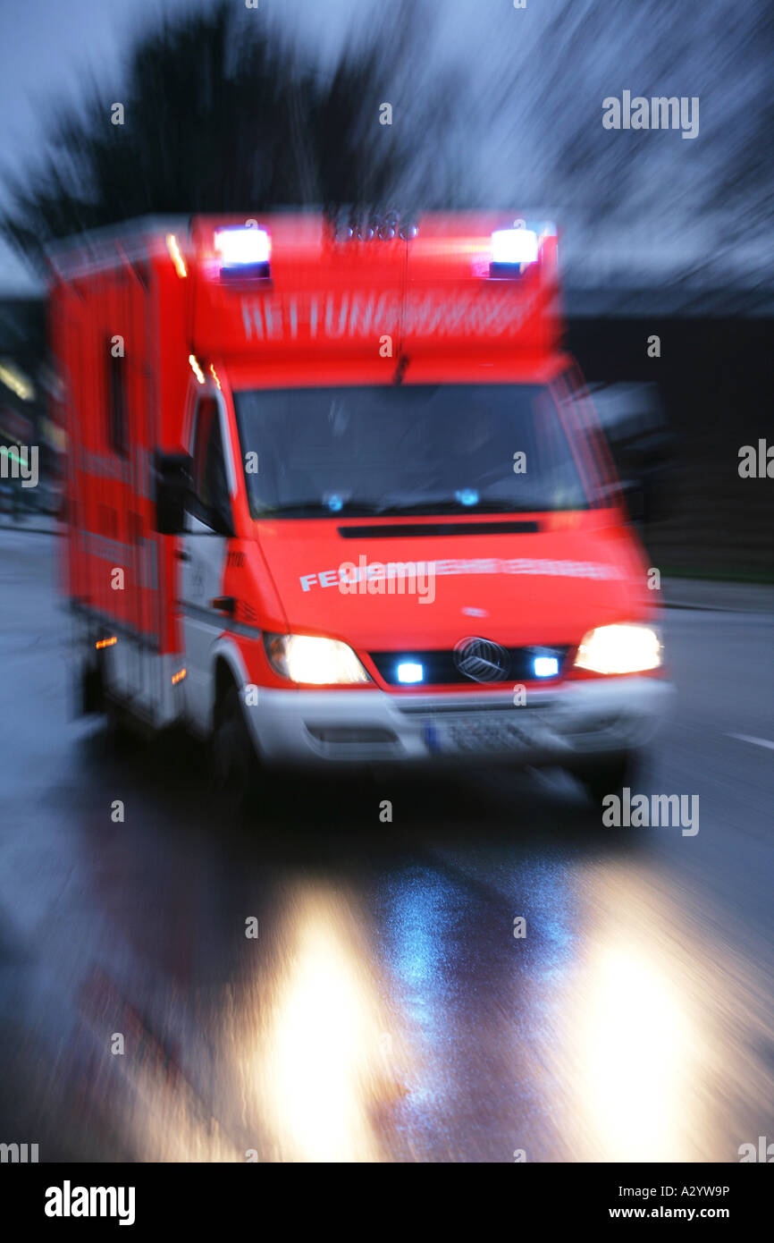 DEU Germany Essen fire brigade Ambulance on the way to an emergency with flashing blue lights - Stock Image