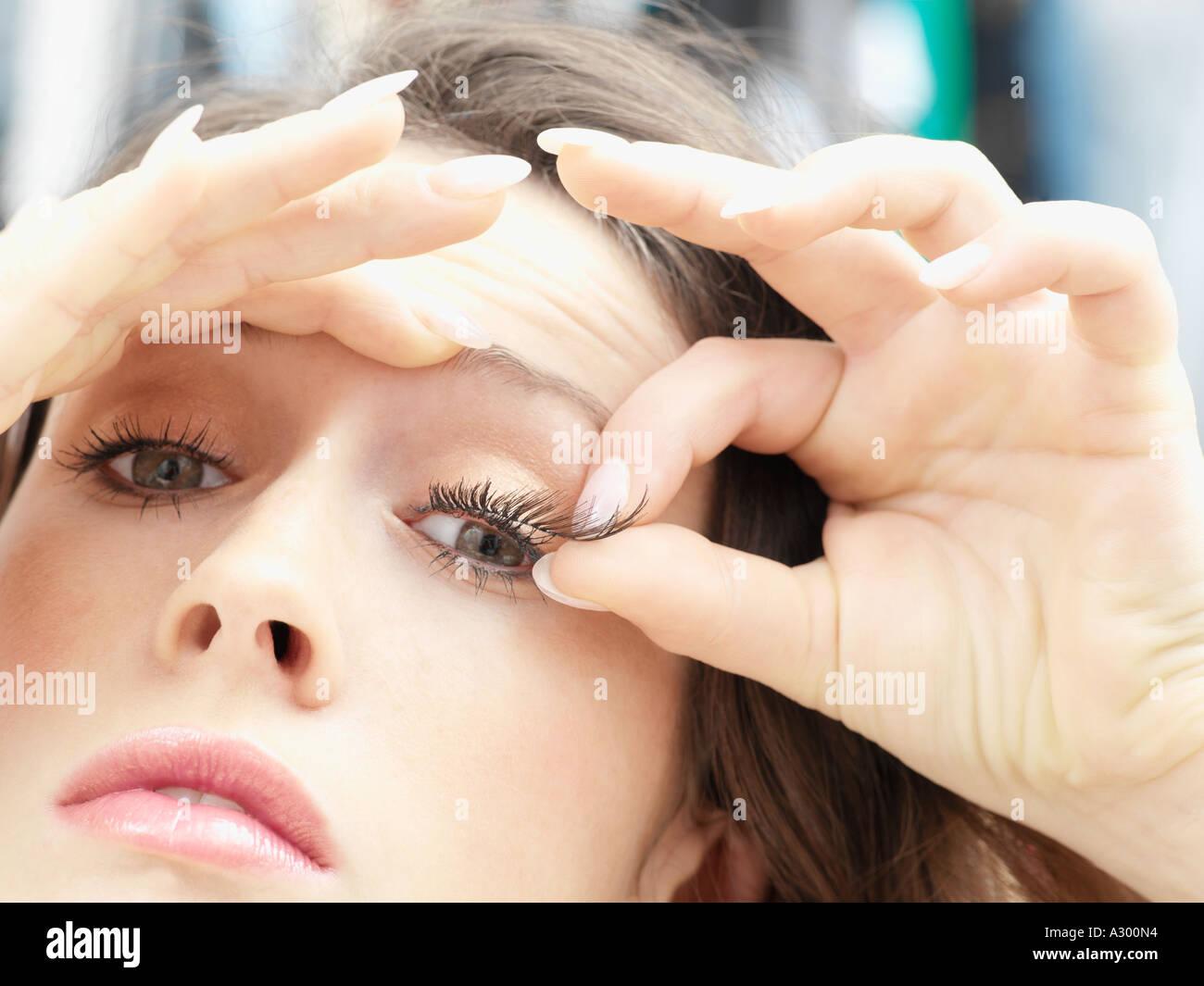 Woman applying fake eyelashes - Stock Image