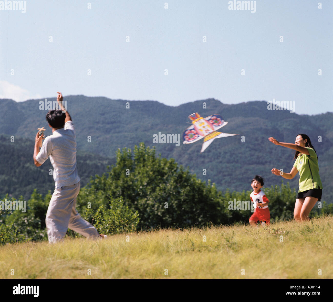 Chinese young couple with their daughter playing kite in outskirt - Stock Image