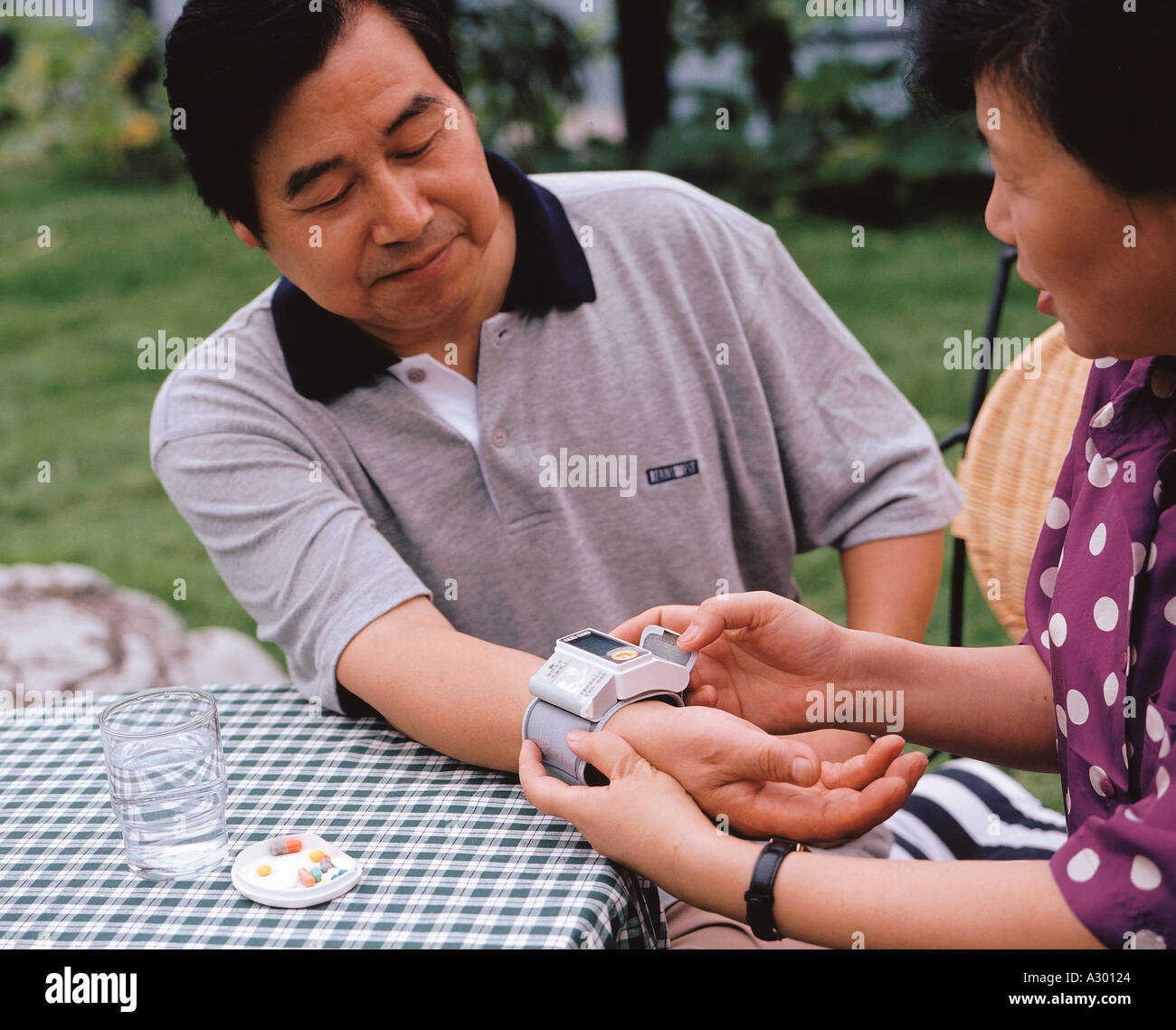 Chinese wife take blood pressure for her husband - Stock Image