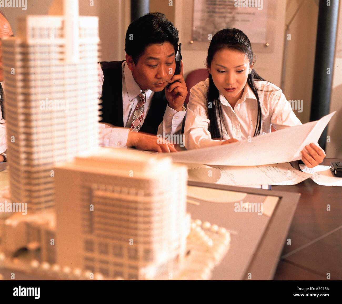 Chinese businessman discussing in front of a building model in a office - Stock Image
