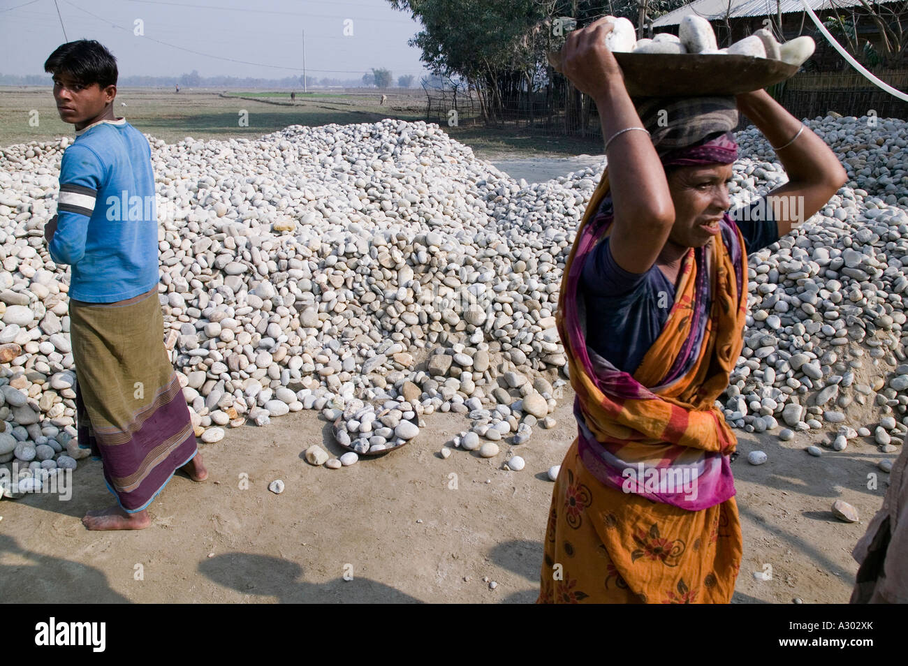 A woman carries large rocks on her head to a machine that will break them down to smaller rocks in northern Bangladesh - Stock Image