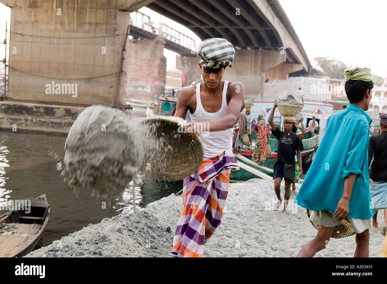 A man dumping out sand he carried from a boat to a pile on land to be sold Bangladesh - Stock Image
