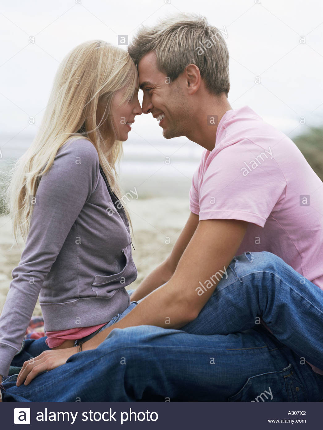 Couple sitting by ocean - Stock Image