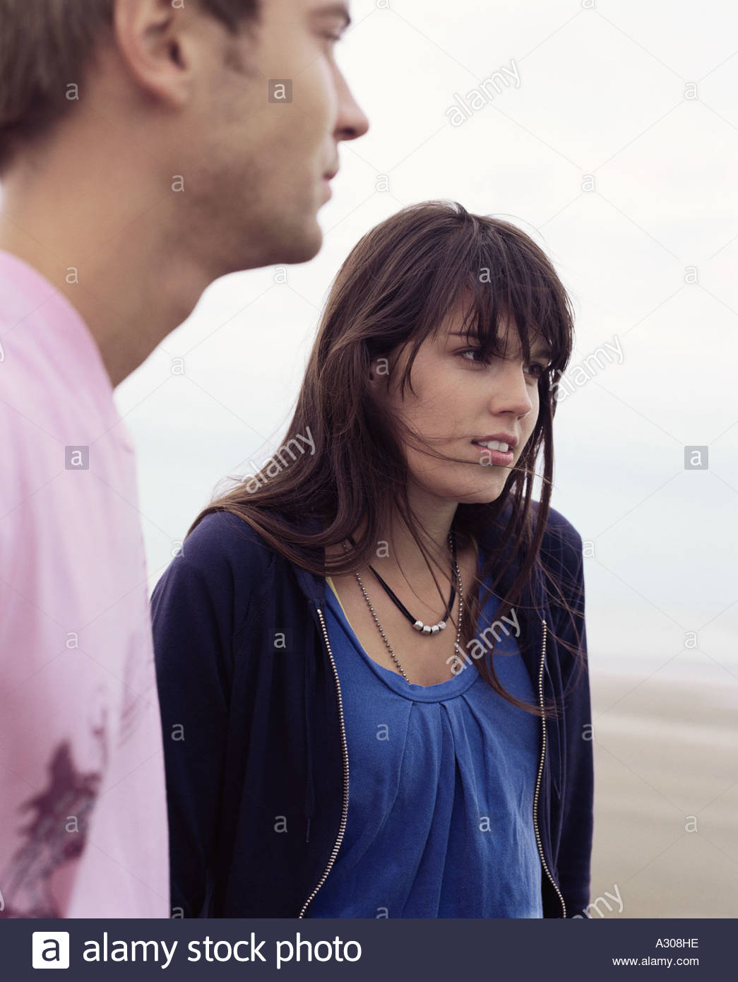 Couple standing by ocean - Stock Image